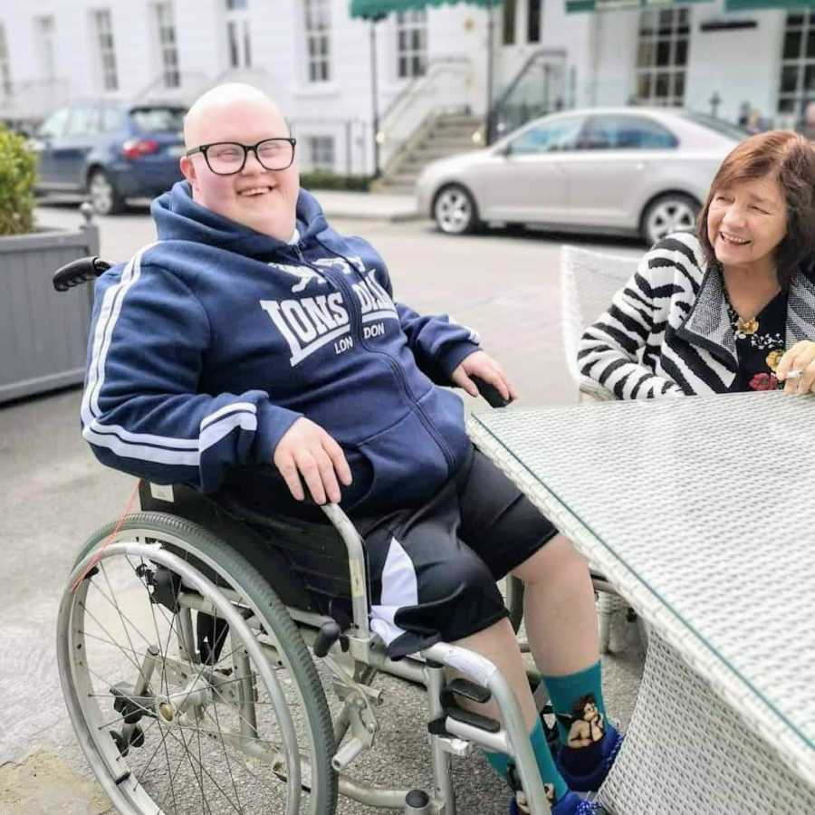 Man in wheelchair sitting at table with woman outside