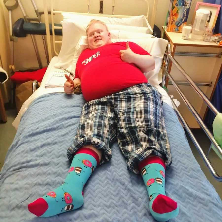 Young man lying in hospital bed wearing patterned socks giving thumbs up