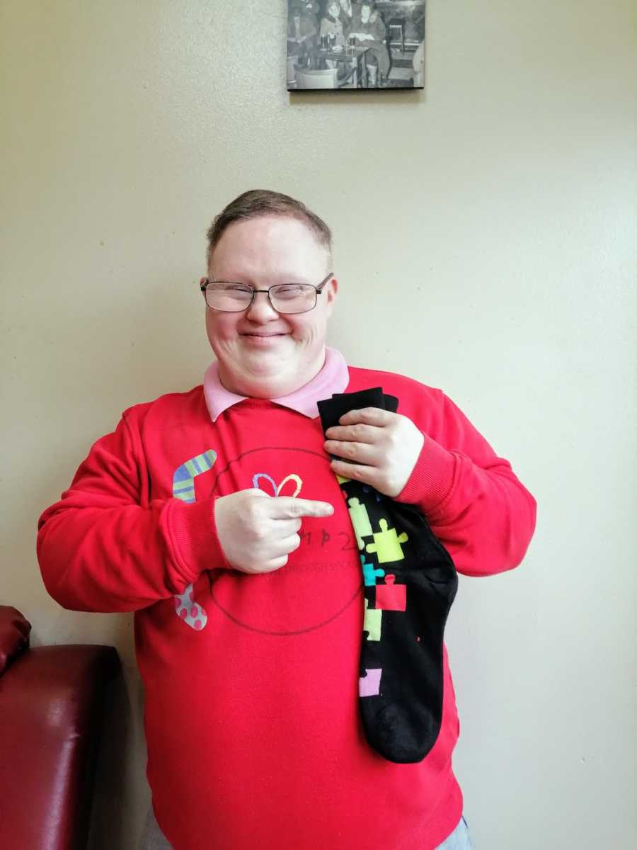 Man wearing red sweater holding up socks with puzzle pieces