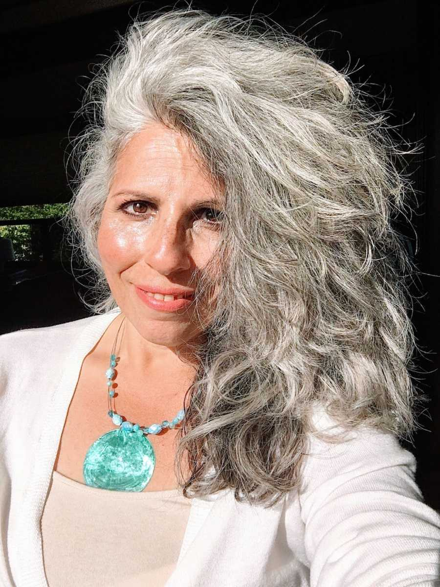 Woman with gray hair wearing blue shell necklace taking smiling selfie in the sunlight