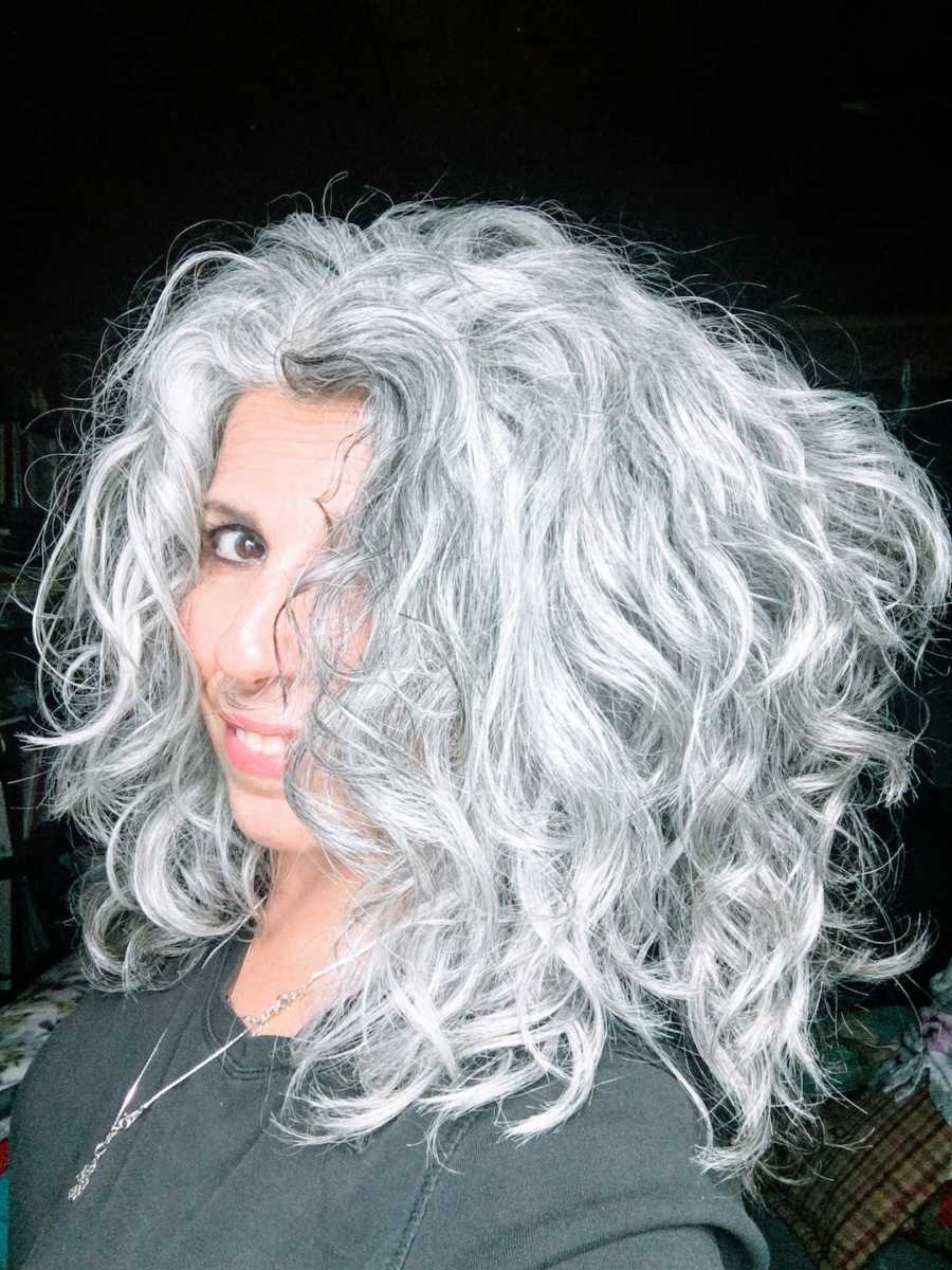 Woman with gray curly hair looking at camera taking a selfie