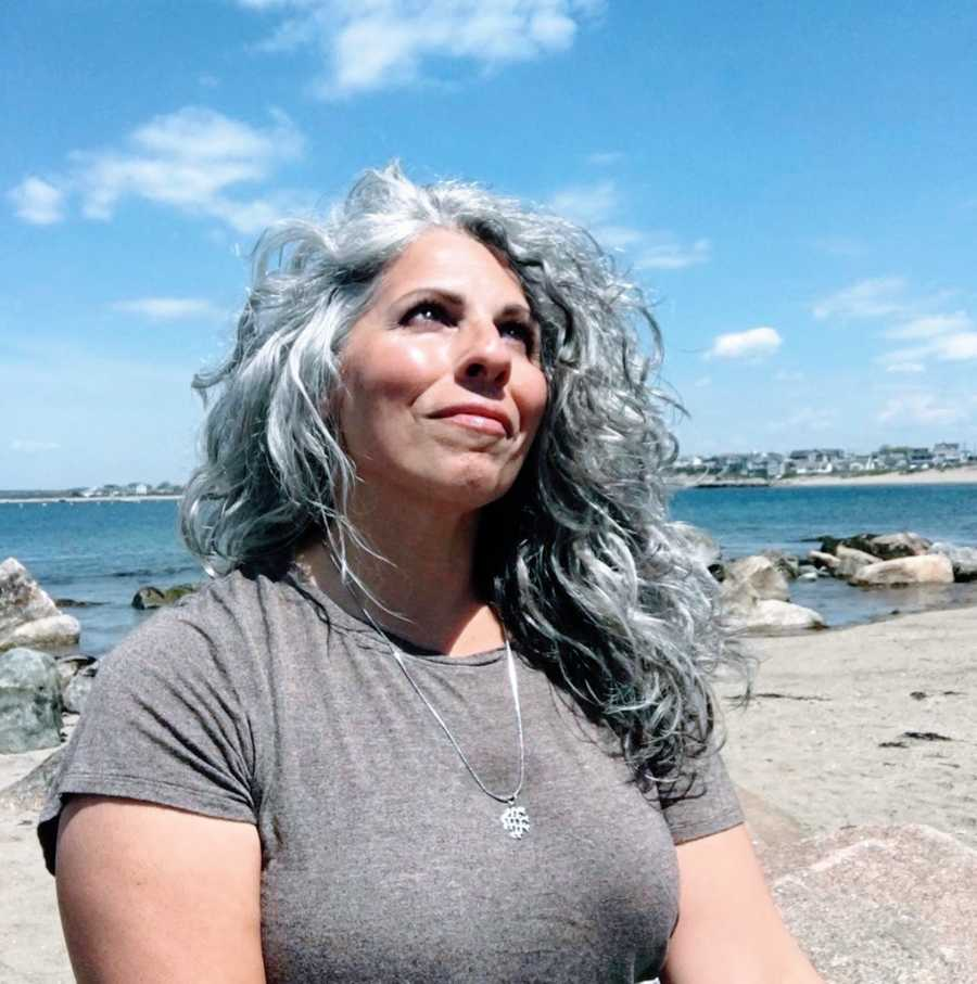 Woman with gray hair looking into sky standing on the beach