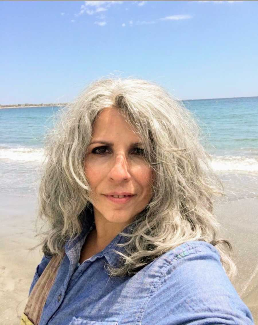 Woman with gray hair taking selfie on the beach