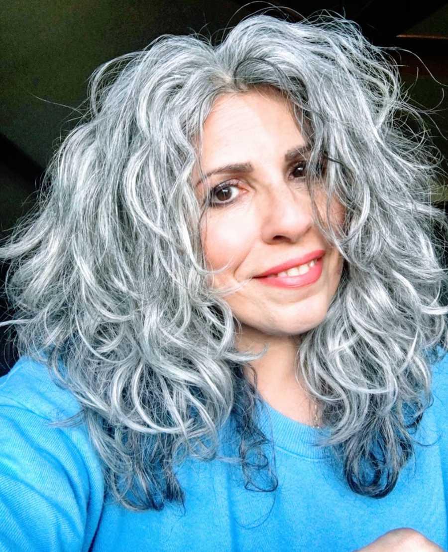 Woman with gray hair wearing blue shirt taking smiling selfie