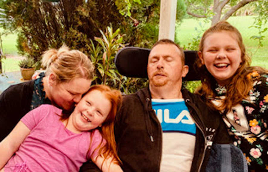 Family of four with father in wheelchair all smiling and laughing