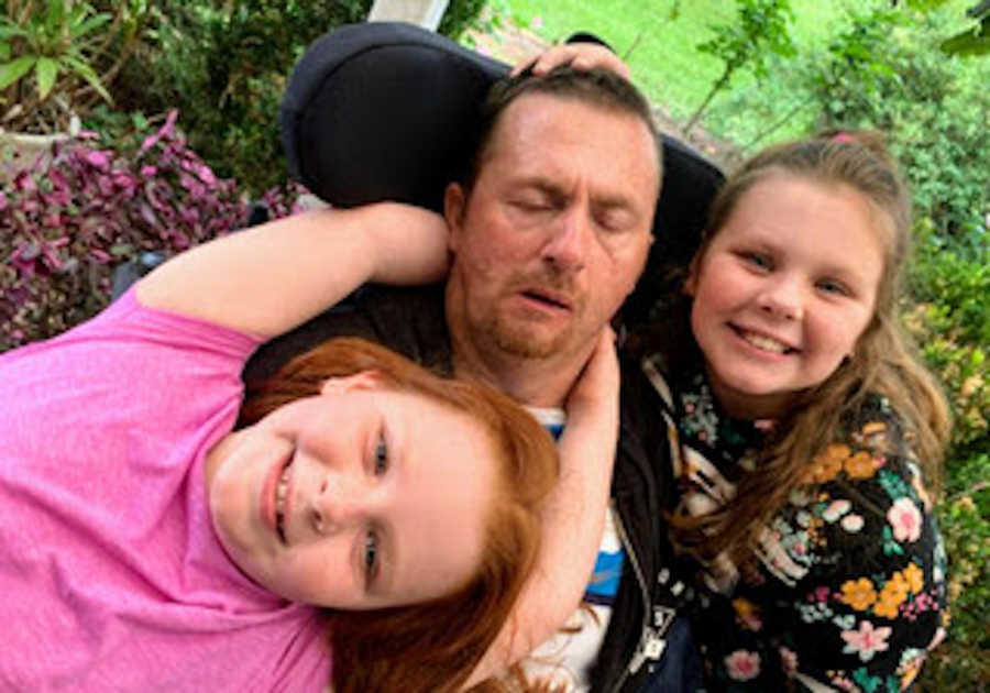 Father in wheelchair being hugged by two daughters