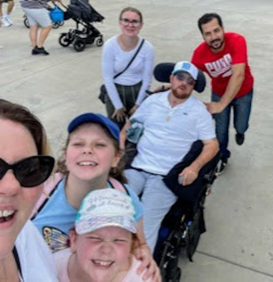 Family with father in wheelchair smiling outside