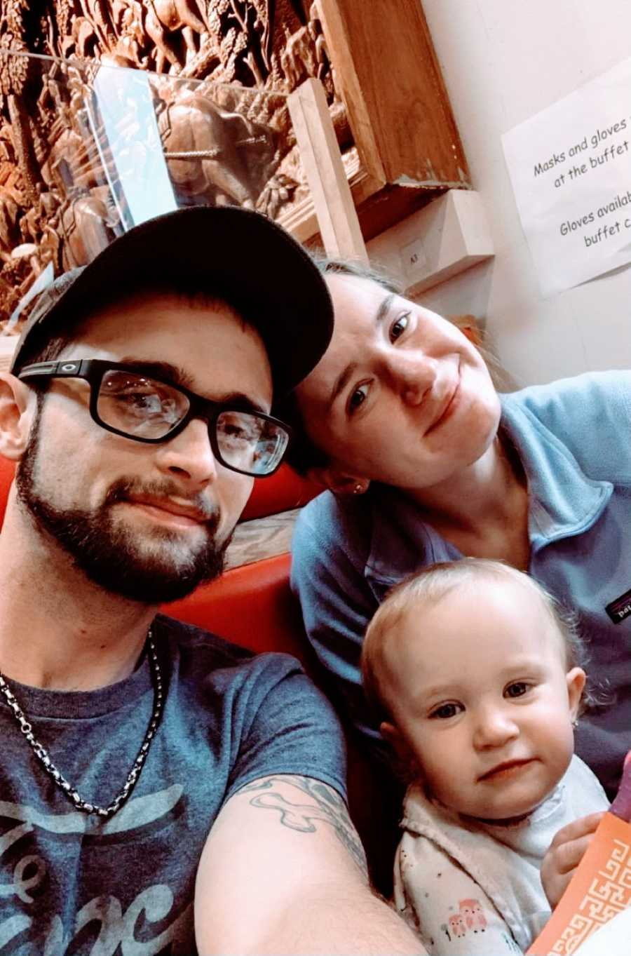 Family of three take a selfie together while out at a buffet for dinner