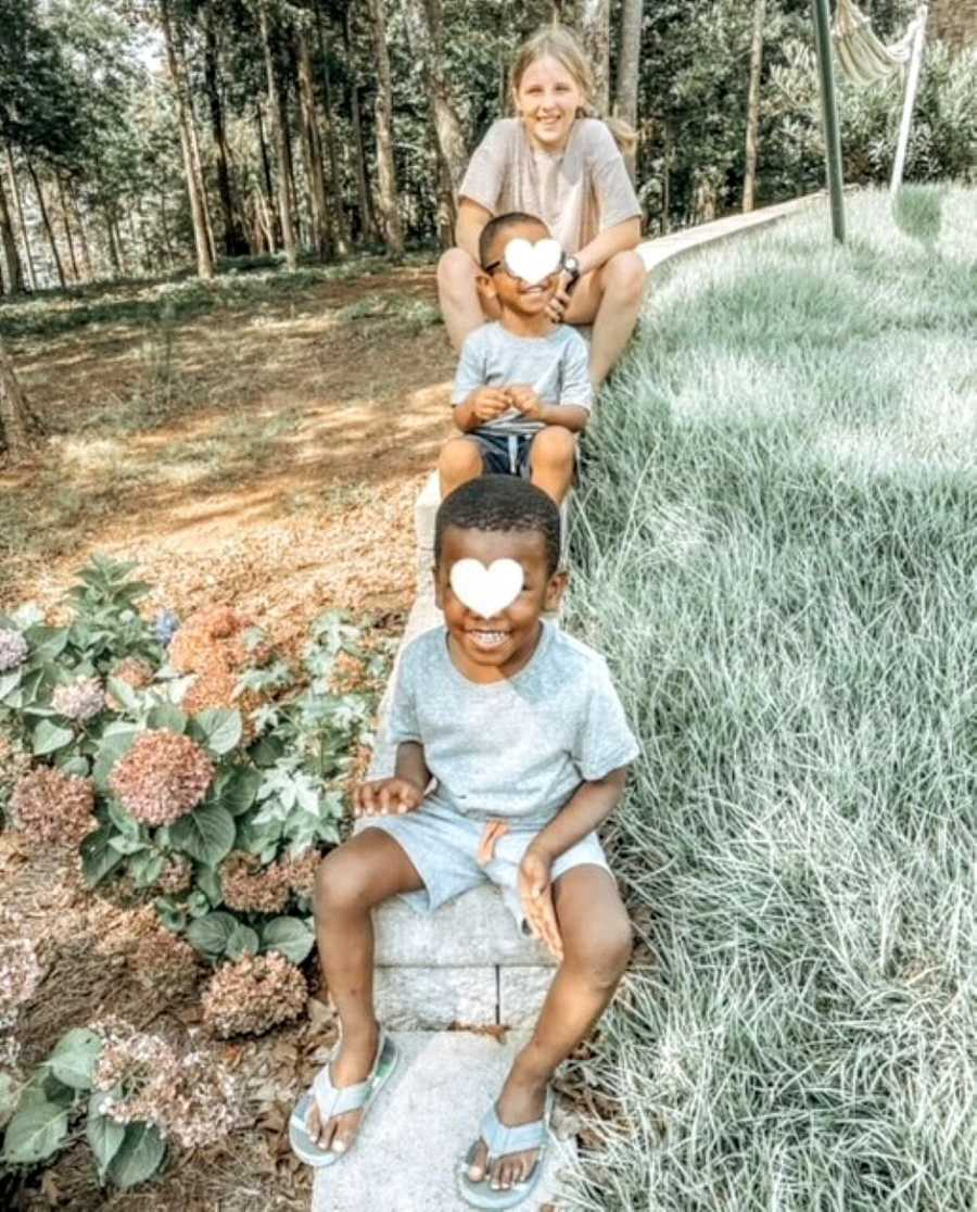 Mom takes photo of her adopted daughter and two foster sons playing in a park
