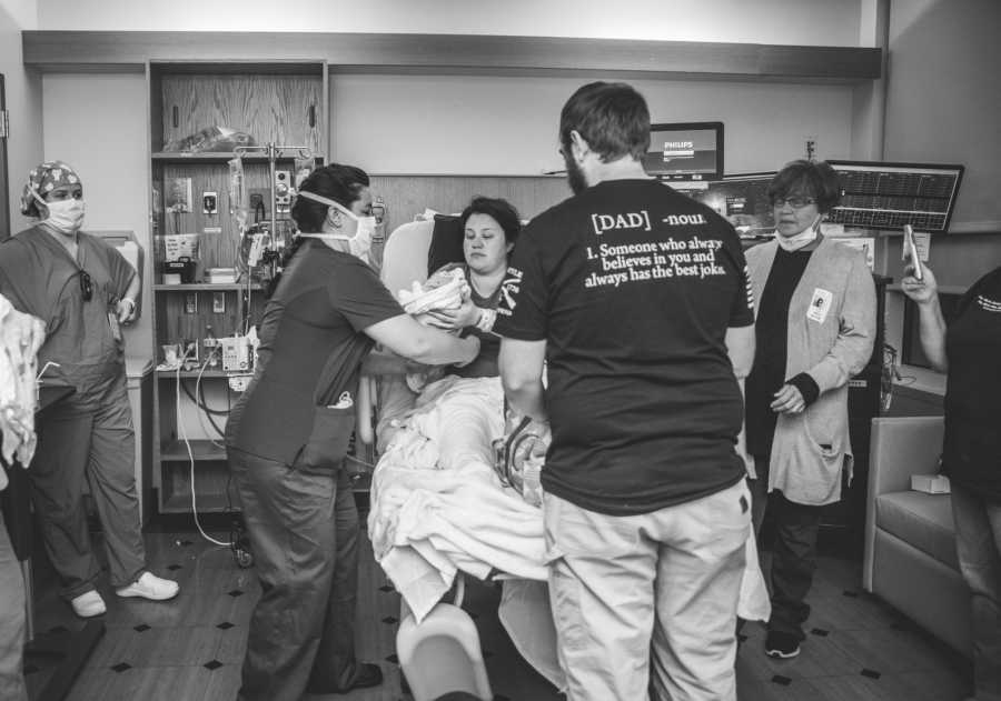 mom and newborn surrounded by dad and doctors