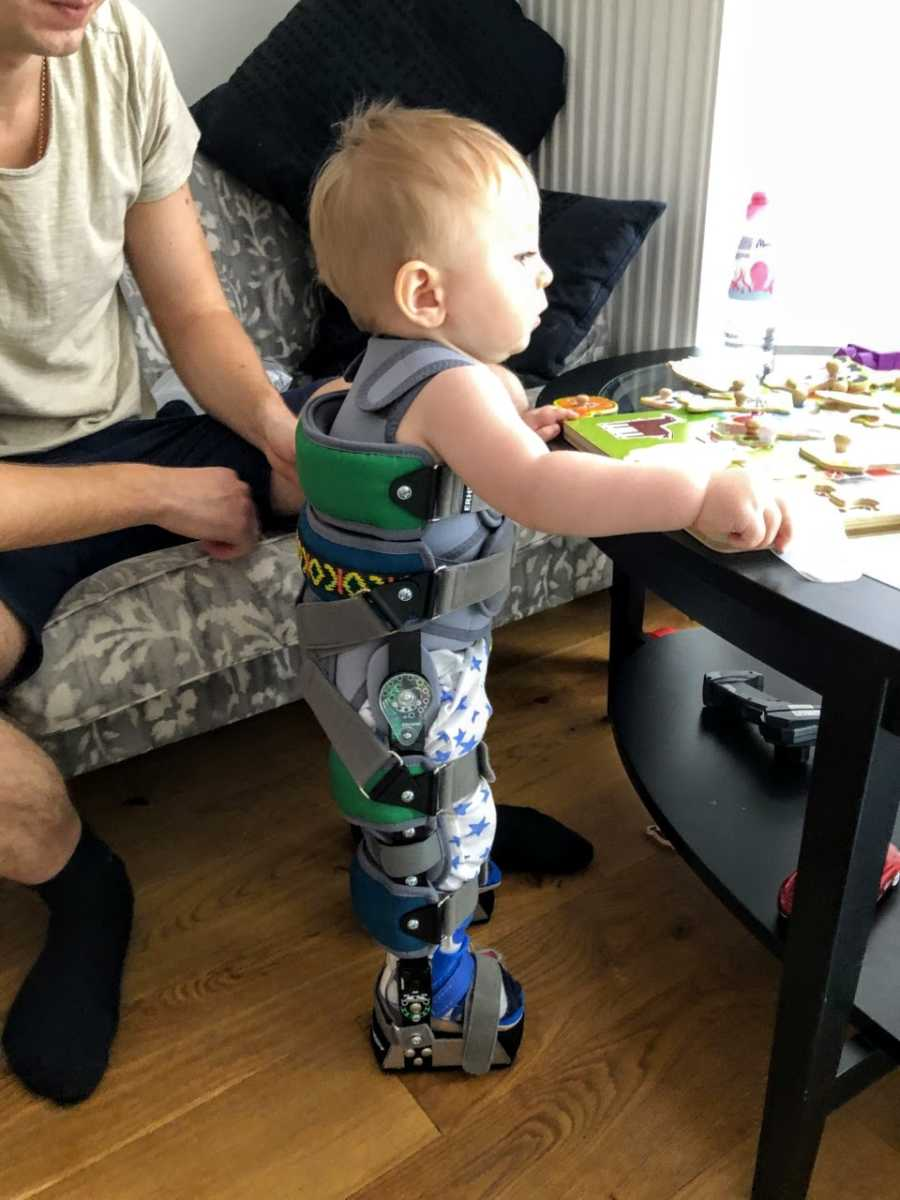 Young boy with spinal muscular atrophy practices standing during a rehabilitation exercise