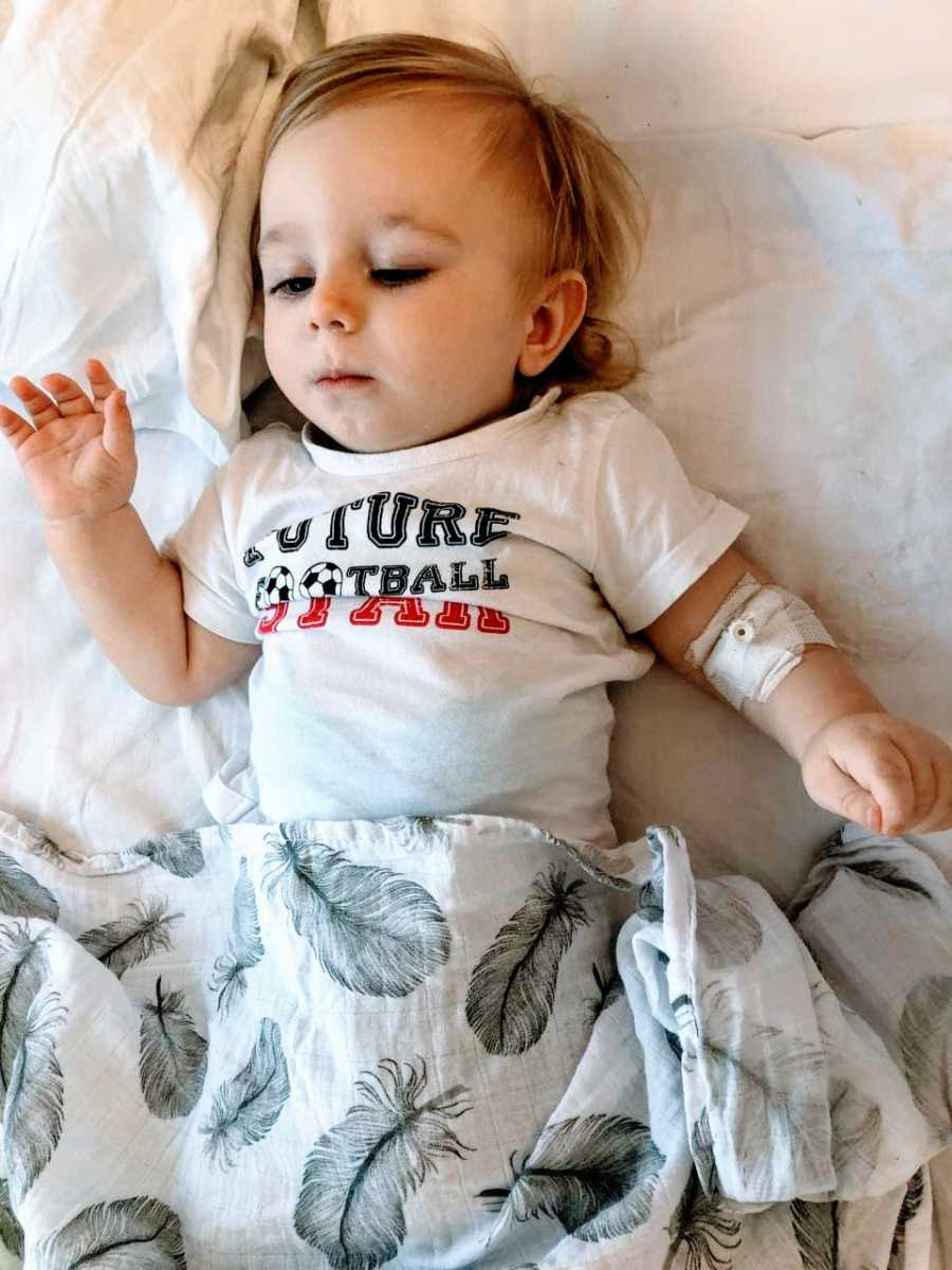"""Little boy with spinal muscular atrophy lays in bed wearing a """"future football star"""" shirt"""