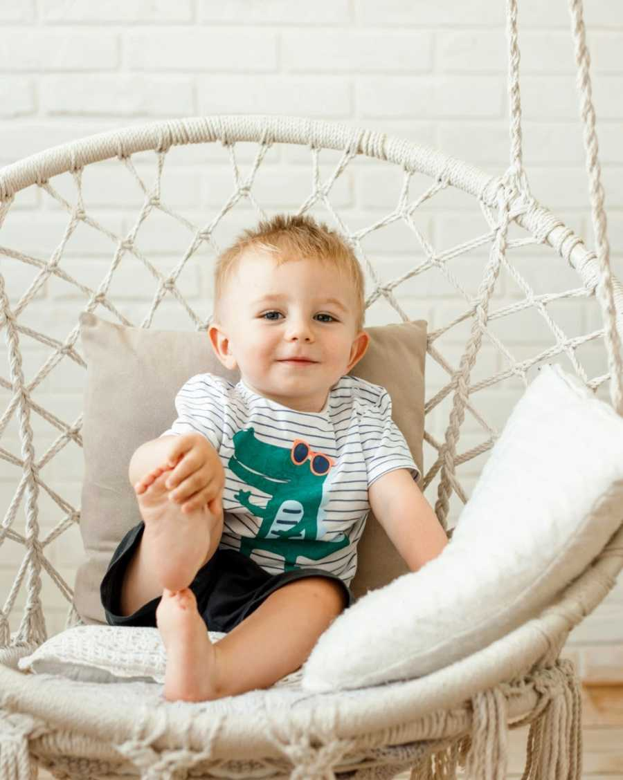 Little boy with an alligator shirt on smiles for a photo while sitting in a white swing chair