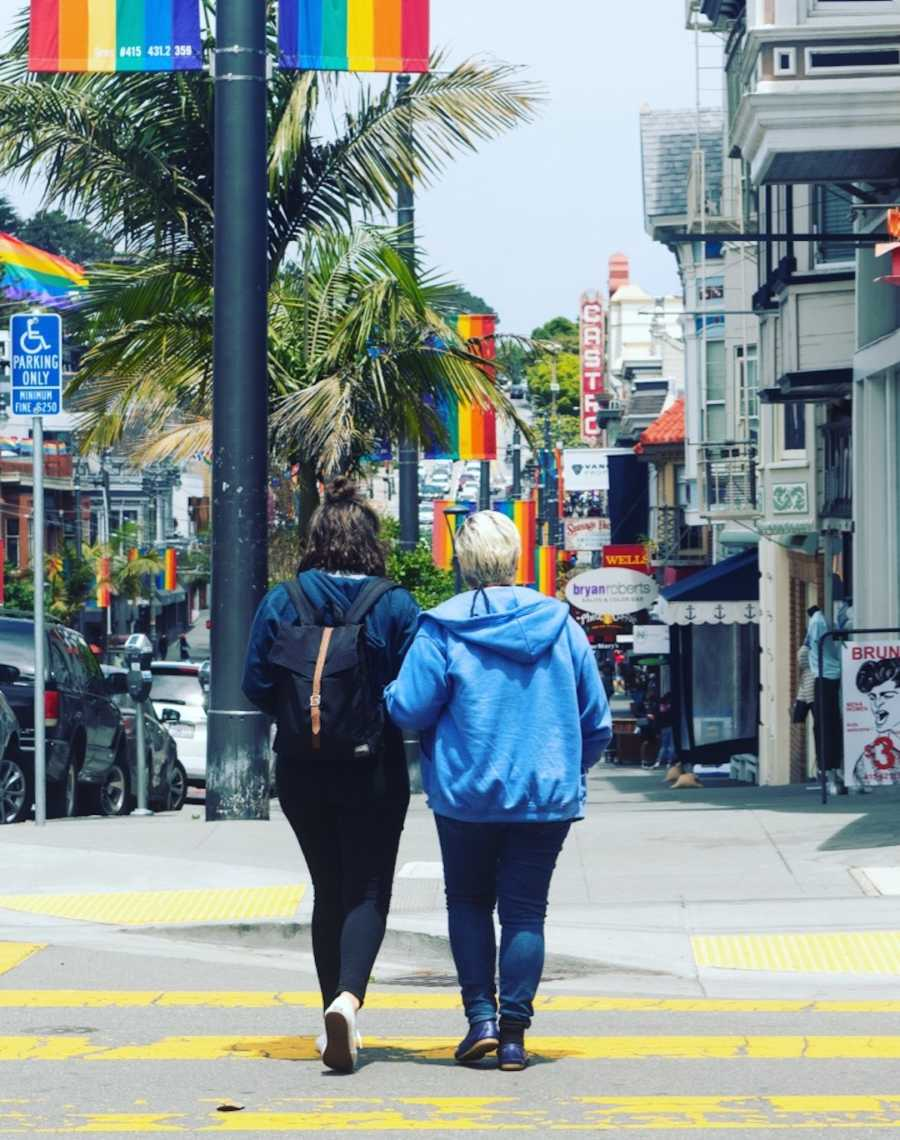 two women walking in street with rainbow flag