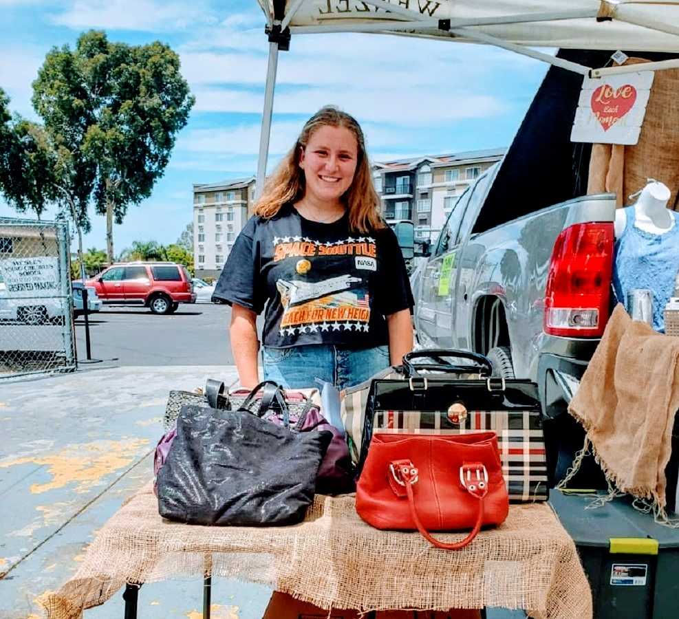 Founder of Purses for a Purpose, Shayna Rutman, in front of donated items.