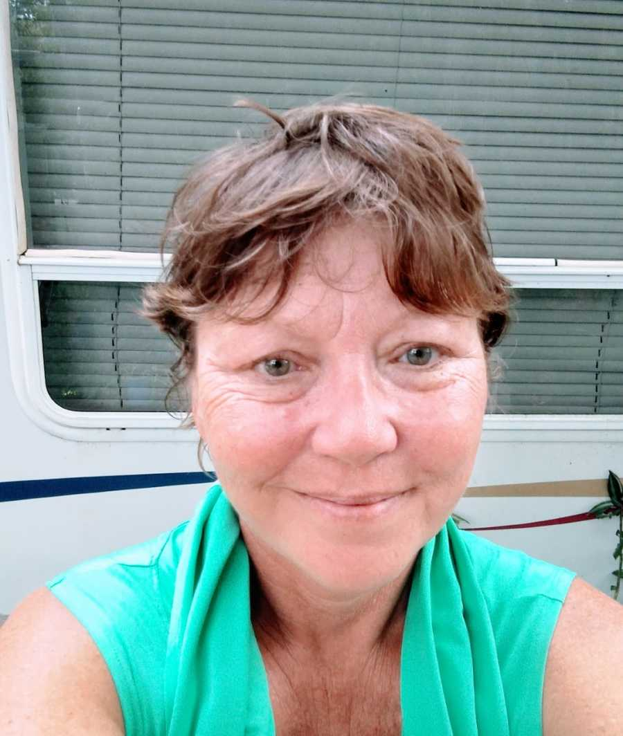 Woman living in Florida takes a selfie outside of her RV camper