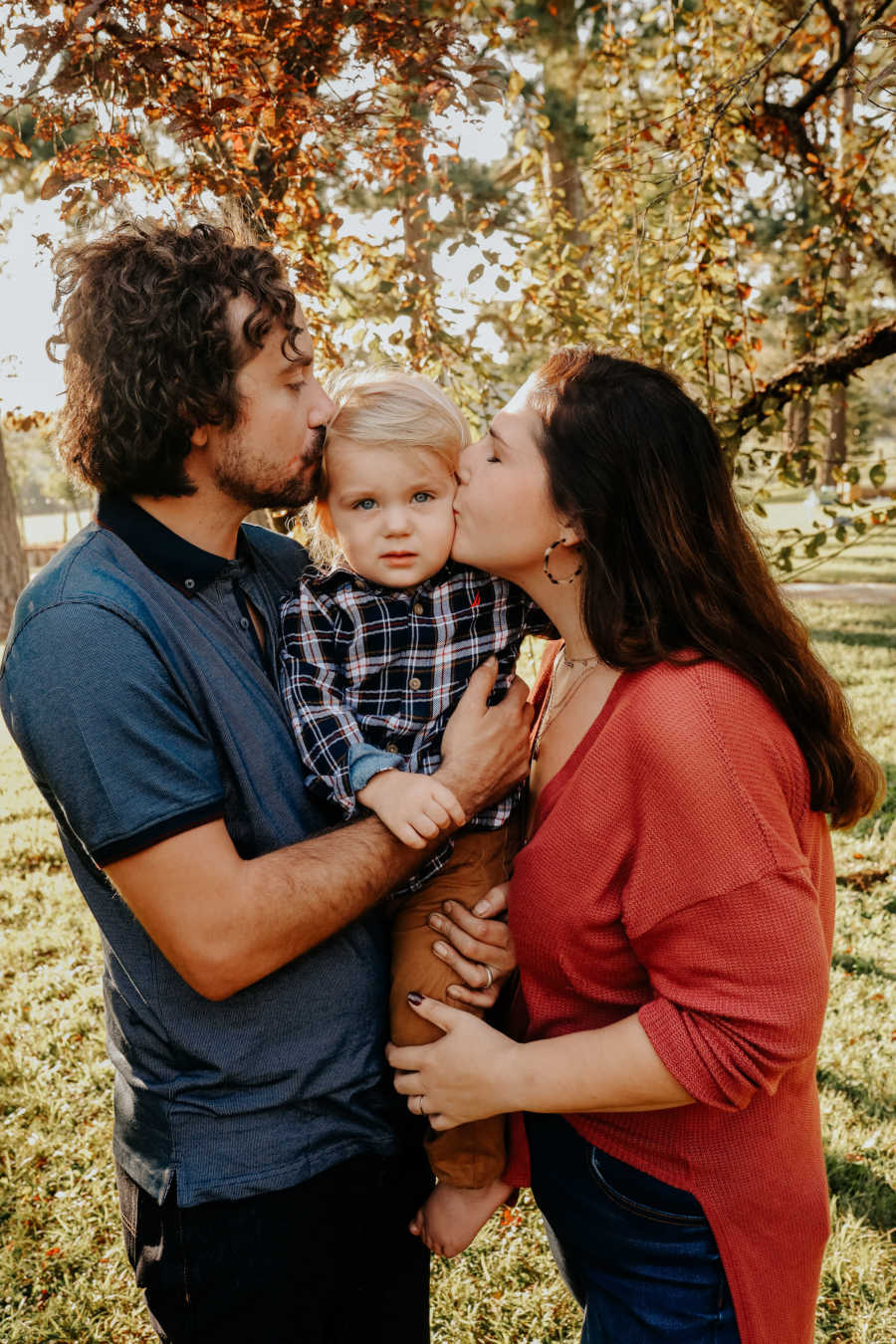 Parents hold their son between them and kiss his cheeks