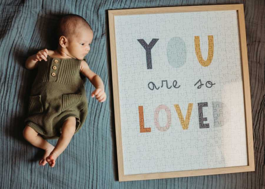Couple take photo of their newborn adopted son next to a puzzle that says 'You are so loved'