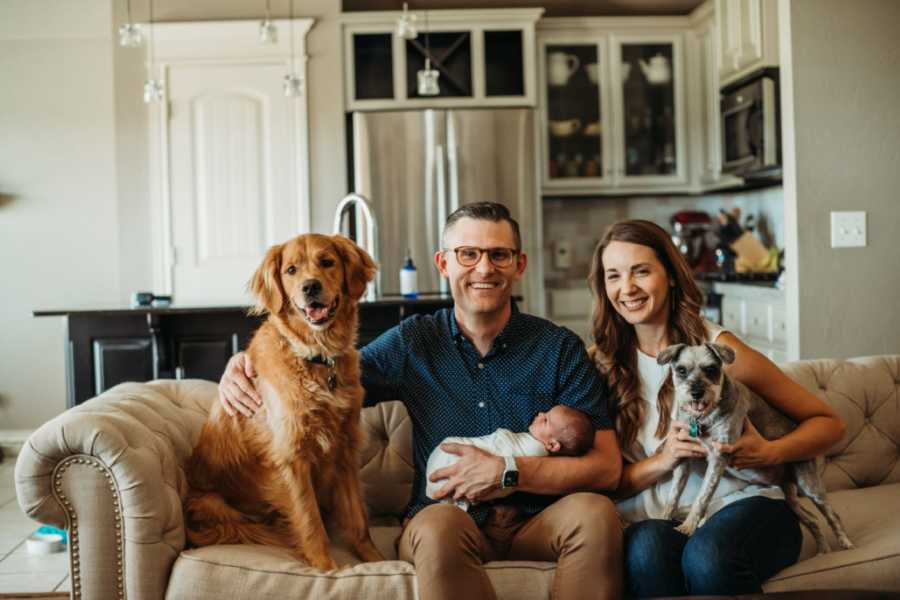 Couple take family photo in their living room with their newborn adopted son and their two dogs