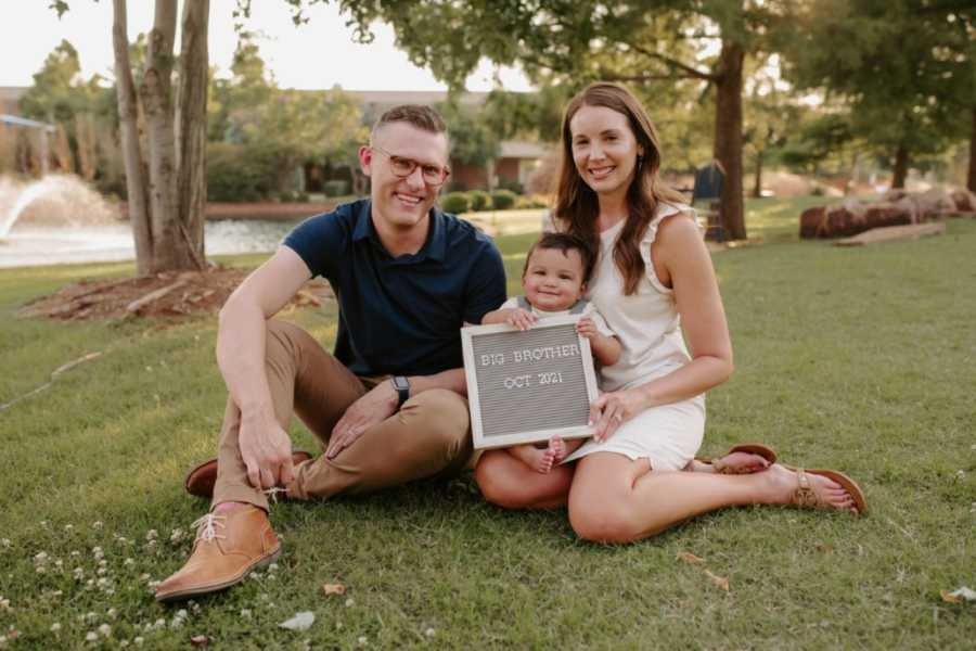 Couple take photo with their adopted son, announcing that they are adopting his baby sibling