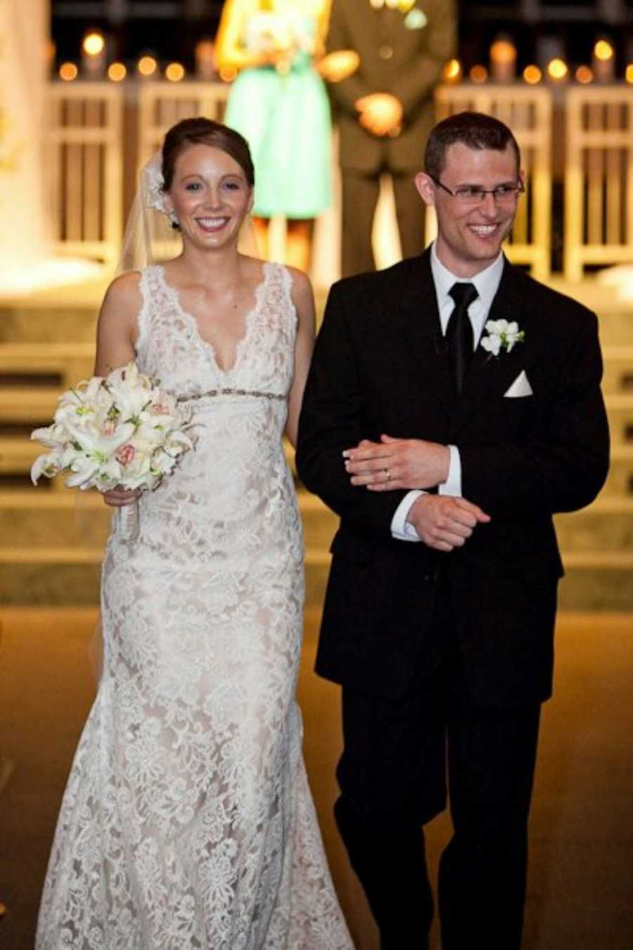 Newly wed couple smile as they walk down the aisle after exchanging their vows