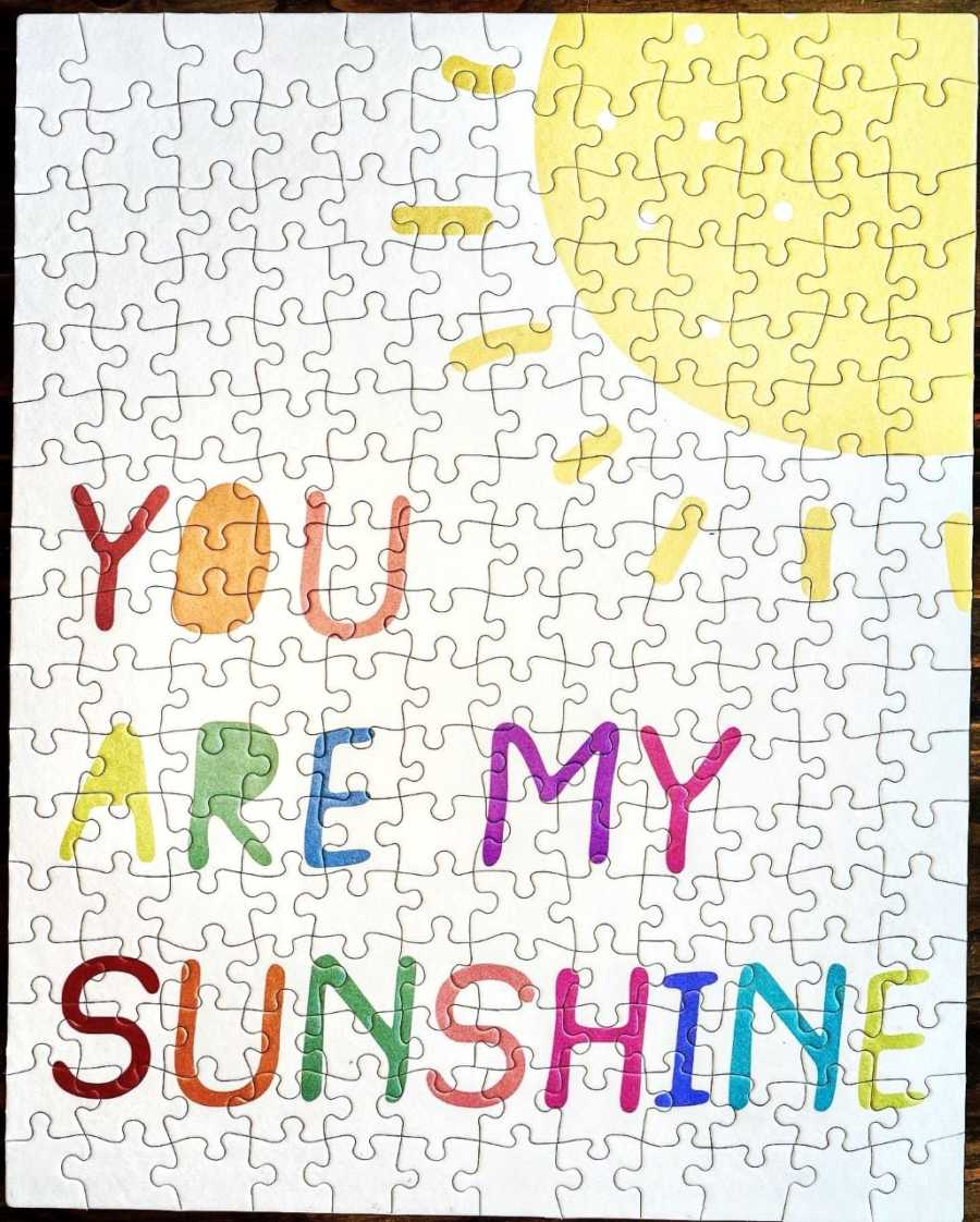 Couple fundraising money for their adoption sell puzzle pieces, the completed puzzle says 'You are my sunshine' with a sun on it