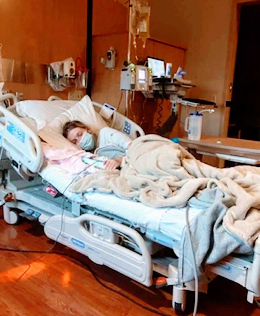 Pregnant woman battling HG sleeps in hospital bed with a mask over her face