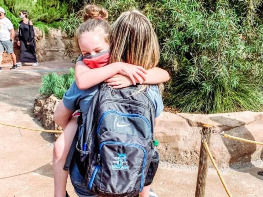 Girl mom proudly holds 9-year-old daughter during a trip at Disneyland