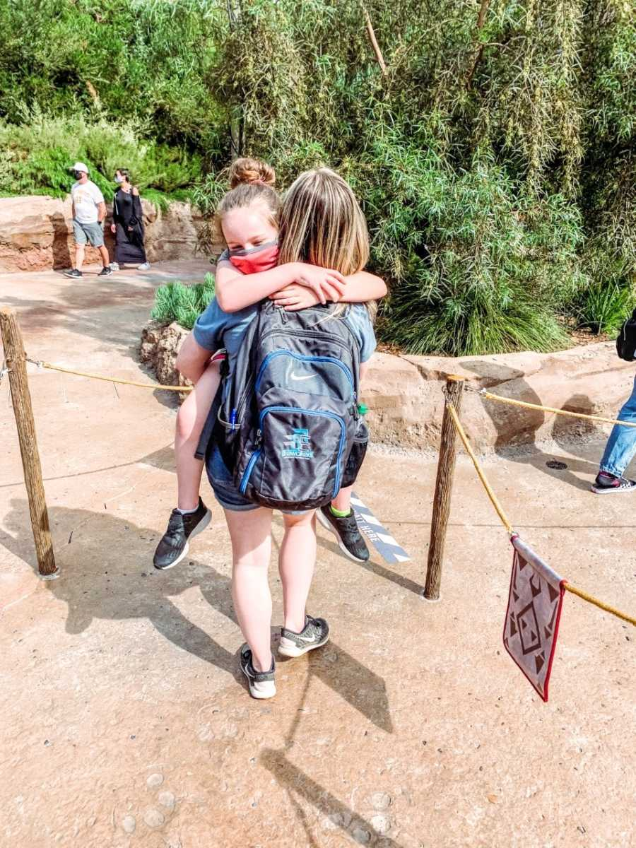 Girl mom holds tired daughter while in line for a ride at Disneyland