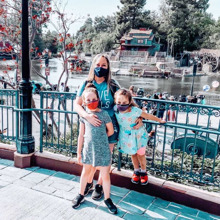Girl mom takes photo with her two daughters while enjoying a day at Disneyland