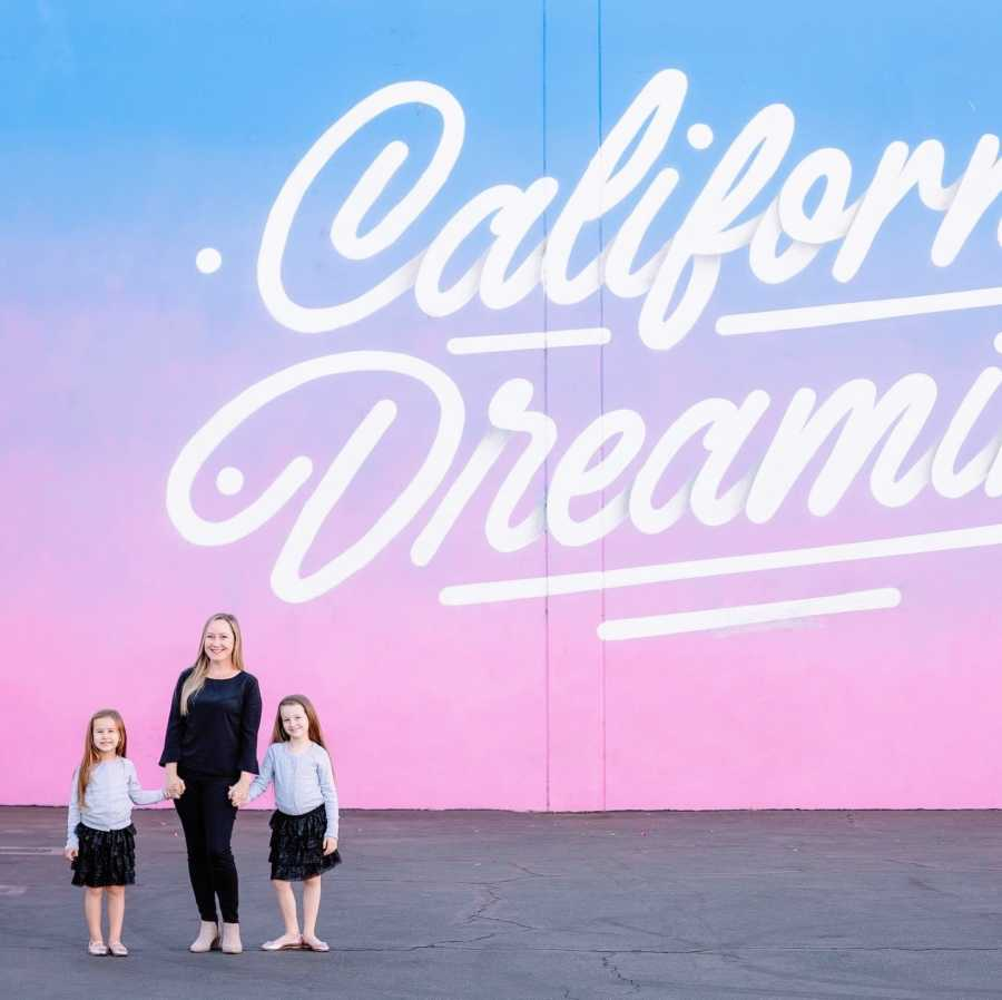 """Mom stands in front of wall mural that reads """"California Dreaming"""" with her two daughters in matching outfits"""