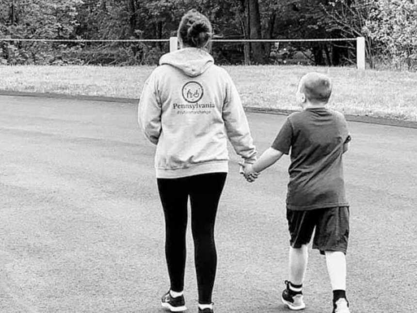 Mom proudly walks with autistic son down the street while holding hands