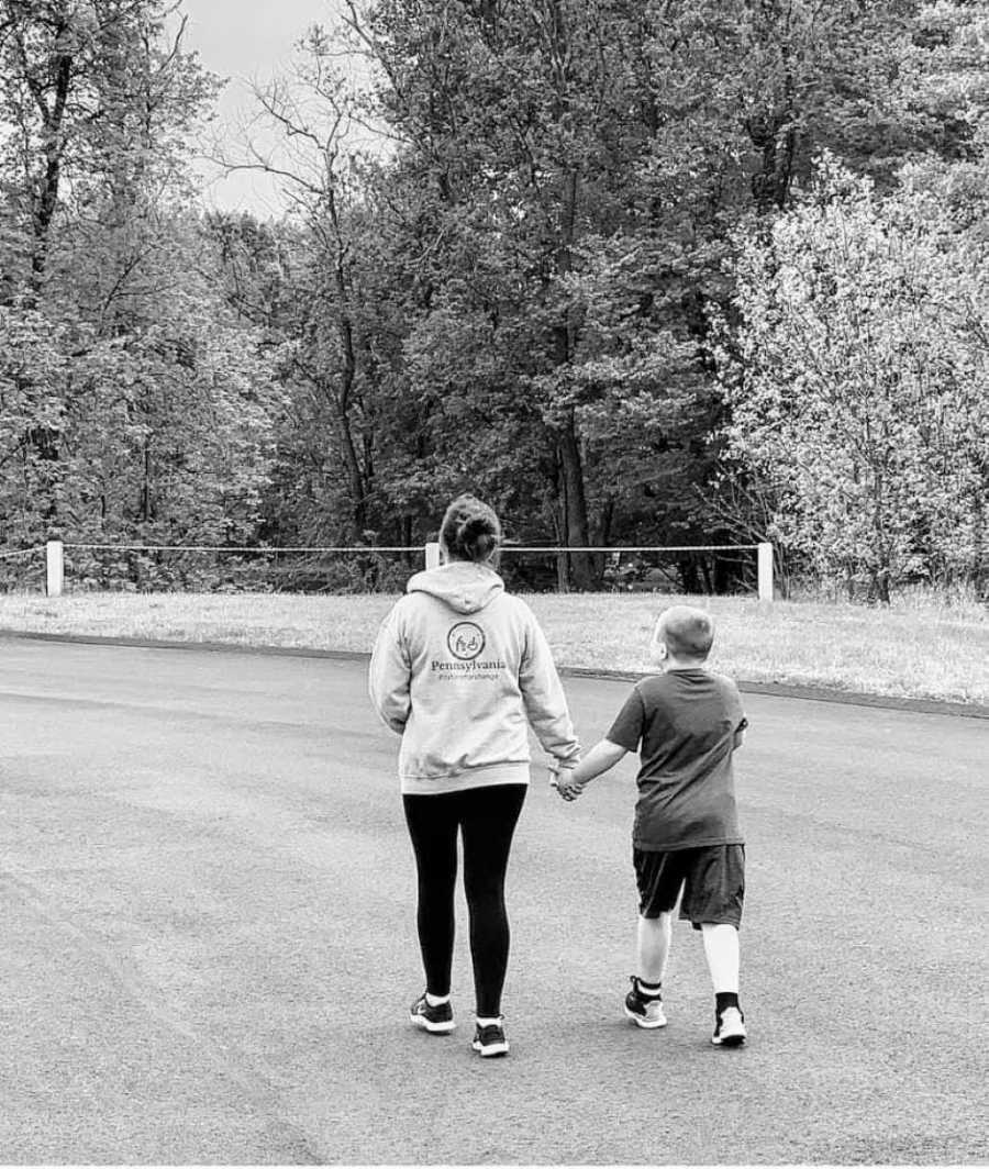 Special needs mom talks a walk with her autistic son while they hold hands