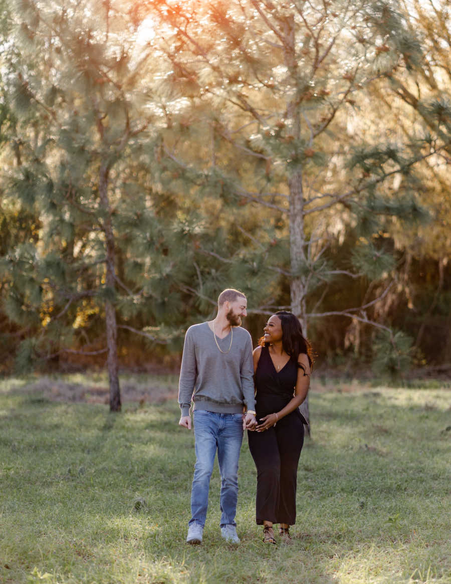 Young interracial couple walk hand-in-hand while smiling at each other, full of love