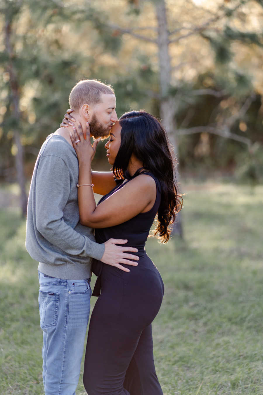 Young man kisses his wife on the forehead in intimate moment during a photoshoot