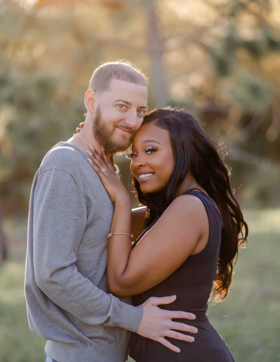 Young interracial couple smile at the camera while embracing each other during a photoshoot