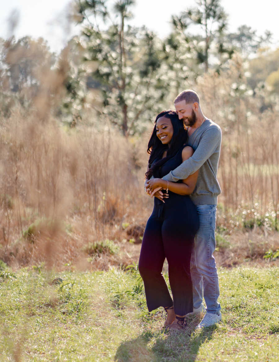 Young interracial married couple embrace in a field during a photoshoot