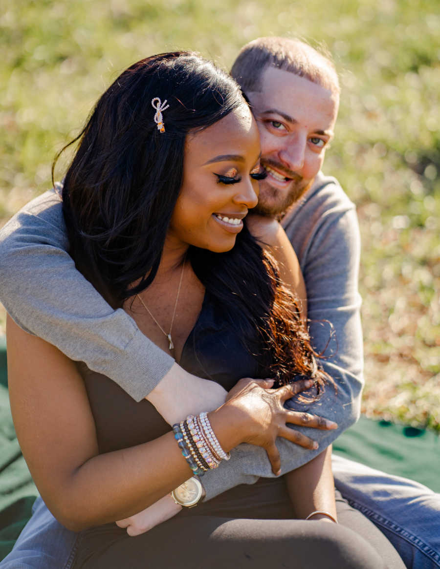 Young interracial couple embrace while sitting down on a green blanket