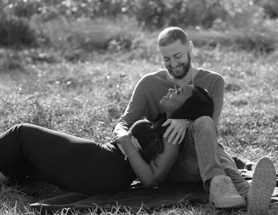 Young married couple lay together in a field during a photoshoot