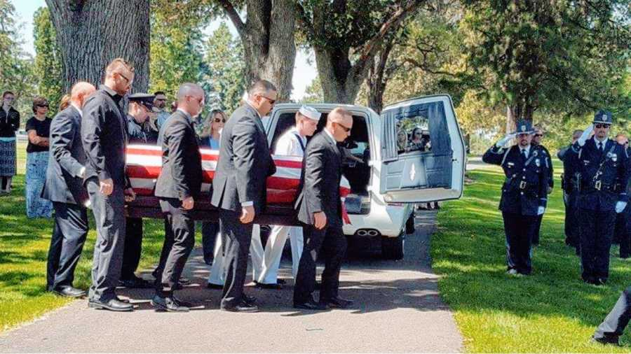 Widow takes a photo of men carrying her late husband's casket