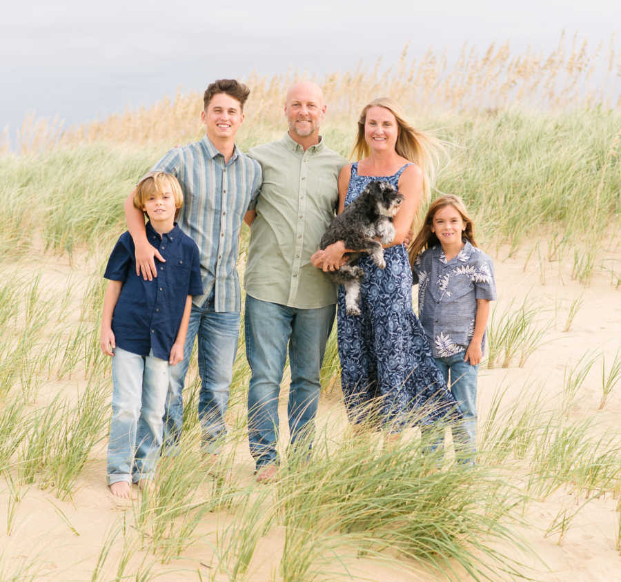 family on the beach dunes with their dog