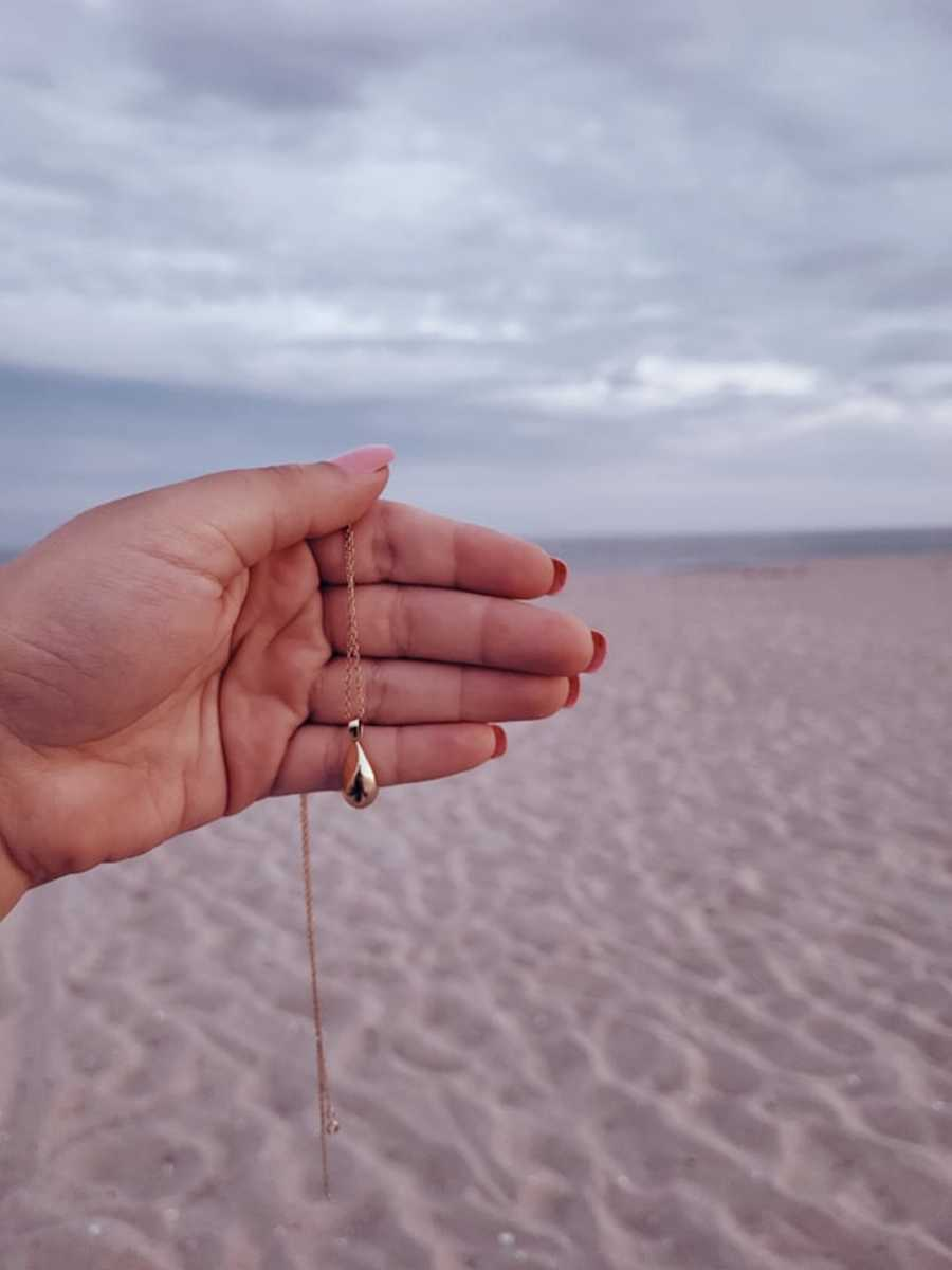 hand holding necklace in front of beach