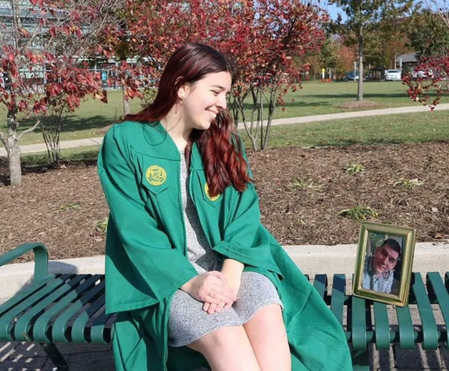 girl in cap and gown with photo of her dad