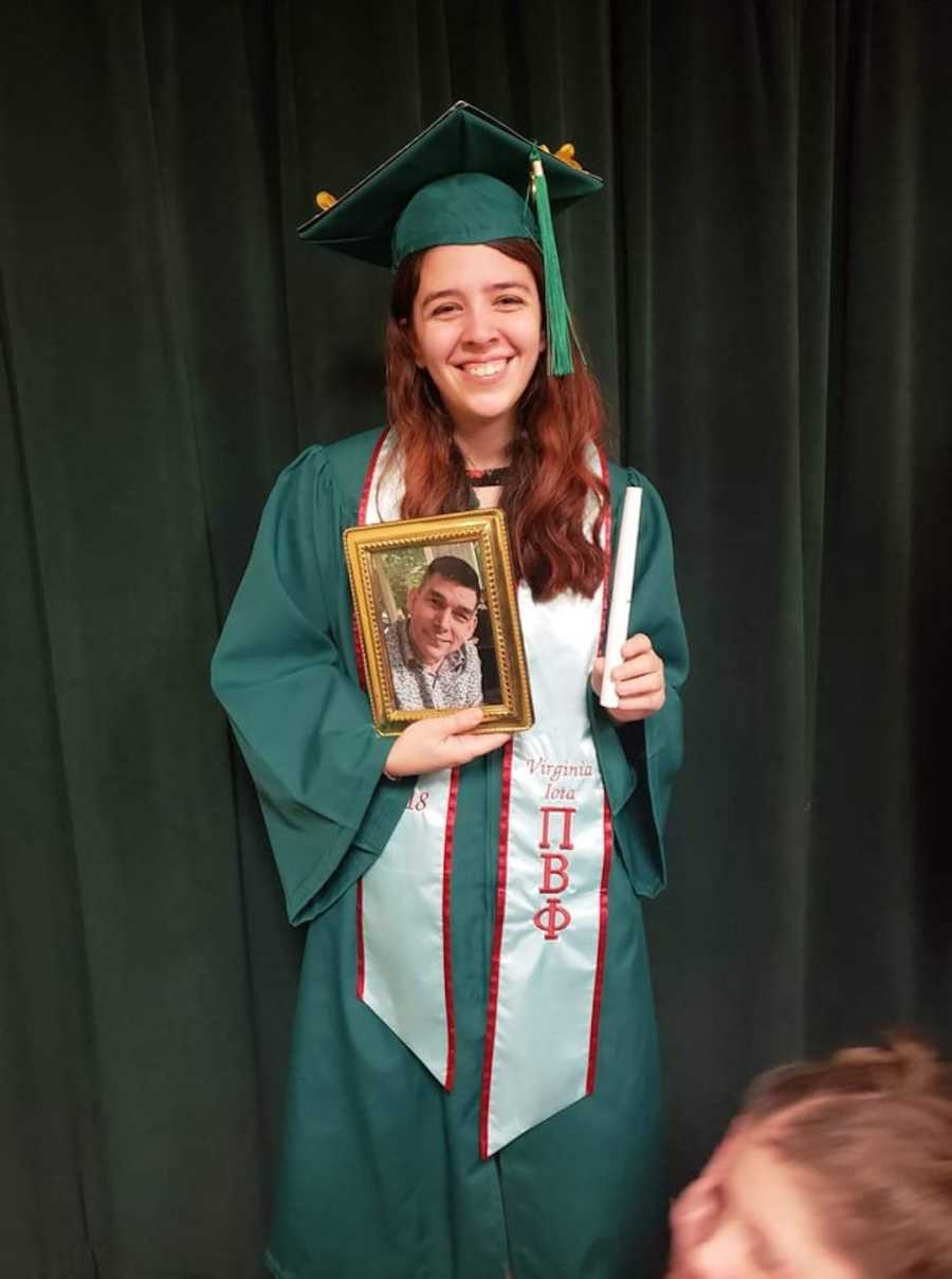 girl in cap and gown holding photo of dad