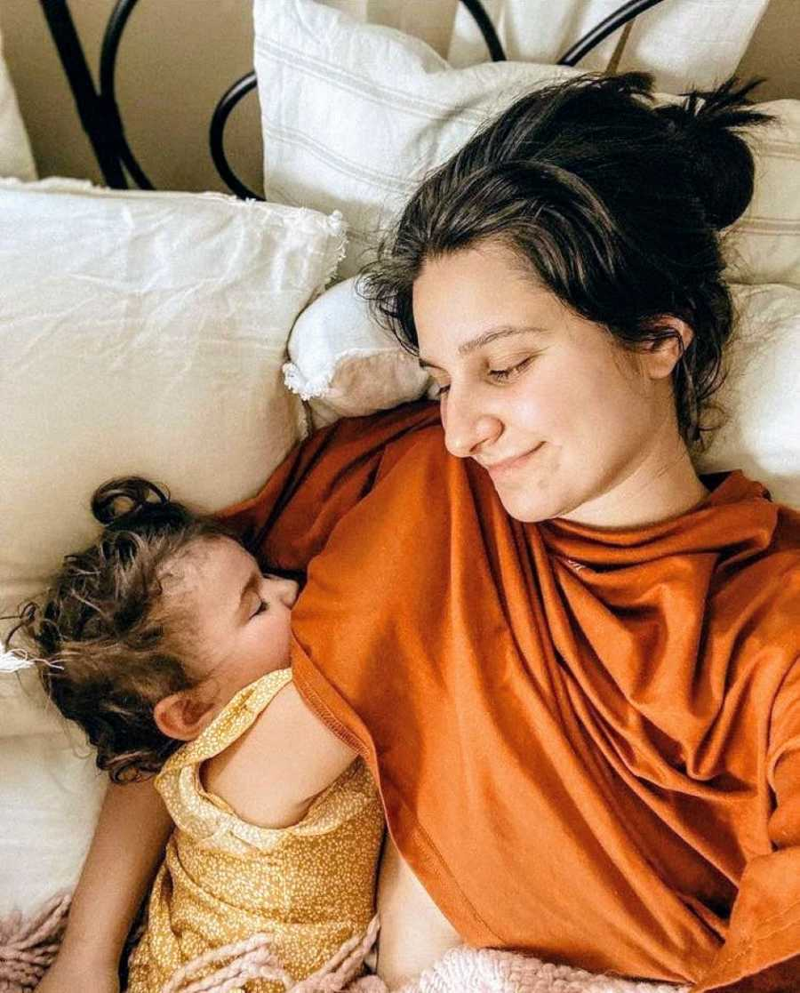 Mom smiles down at her baby girl while they cuddle together in bed during an afternoon nap