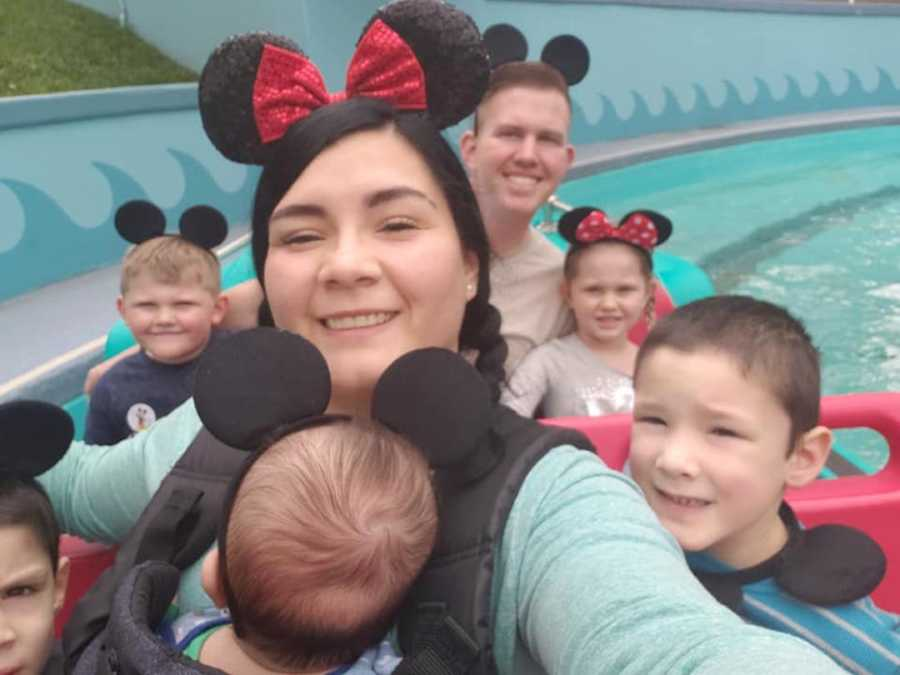 mom in mouse ears on ride with her kids