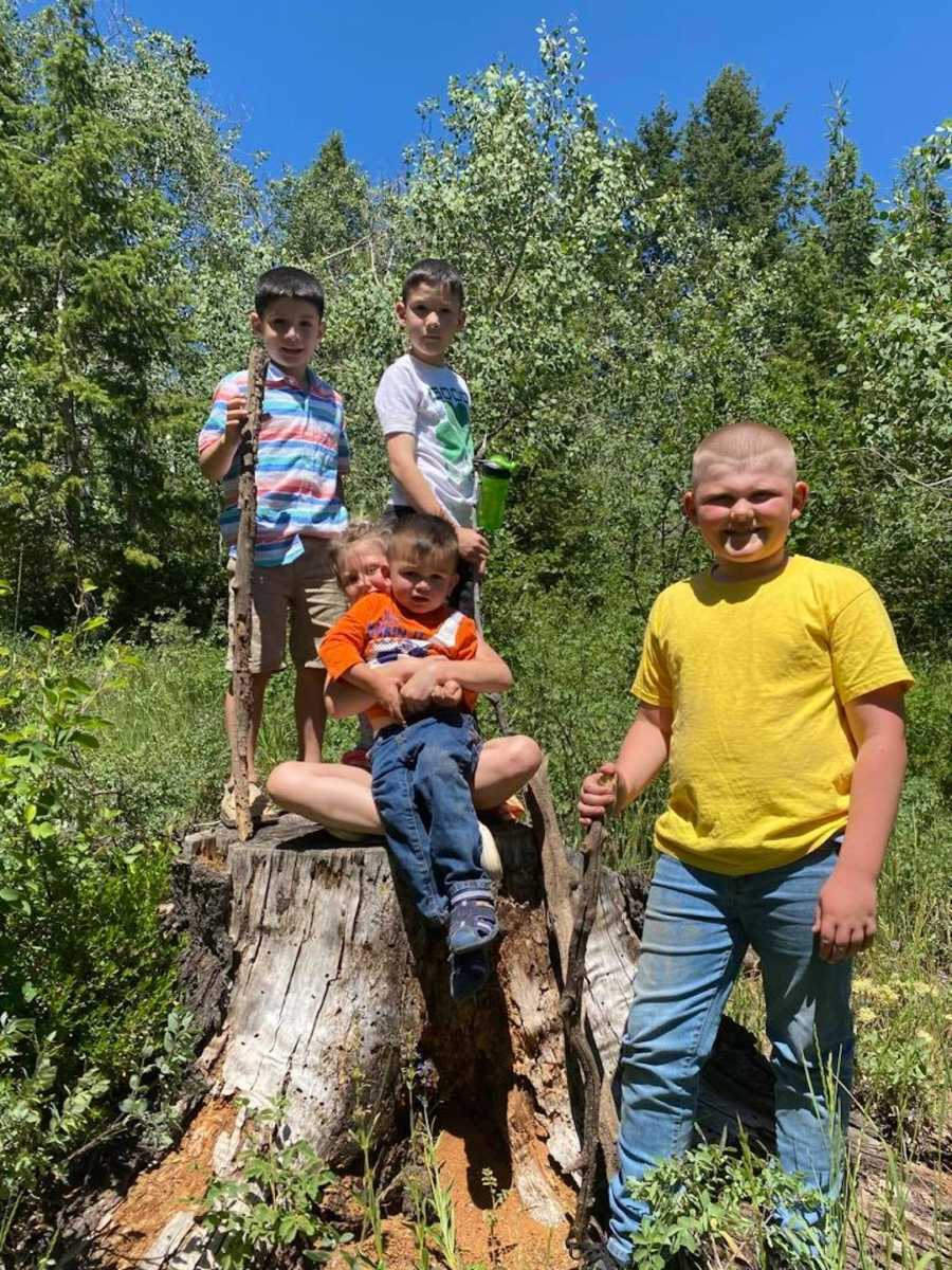 5 kids in the forest on a tree stump