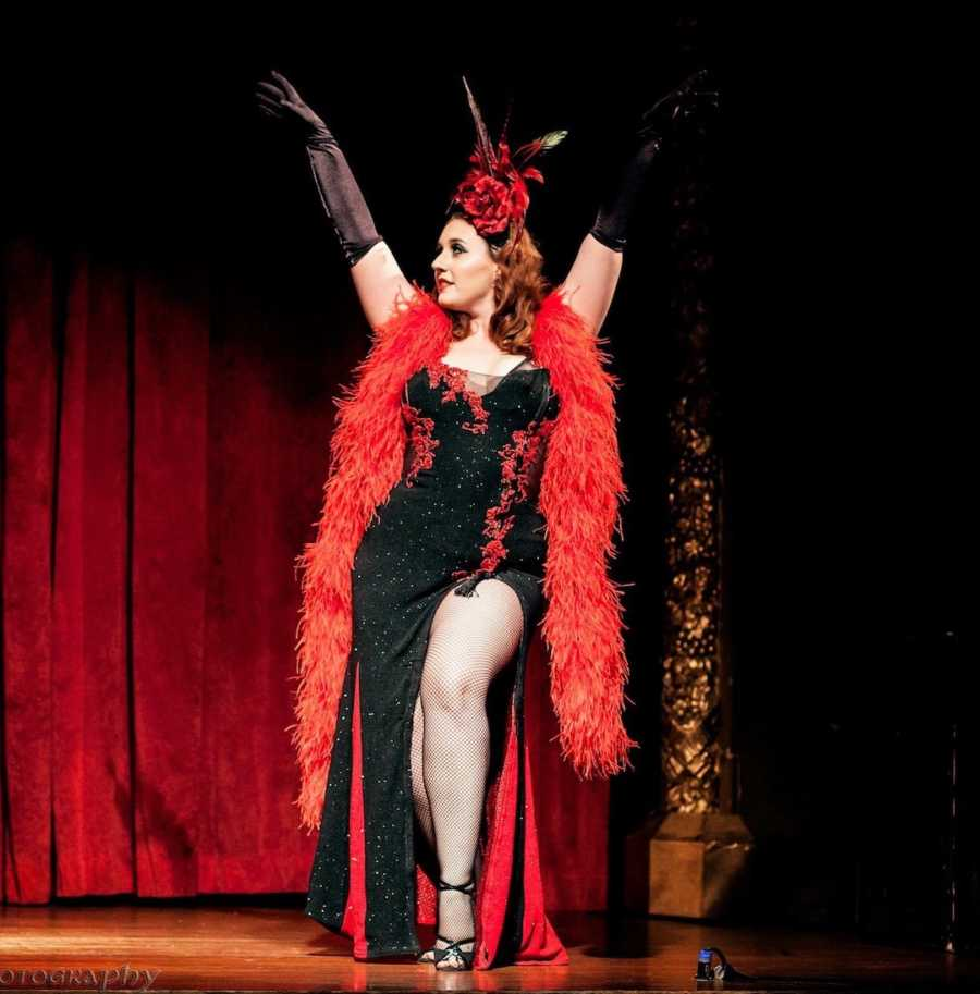 woman in burlesque show wearing a black and red dress with feather boa