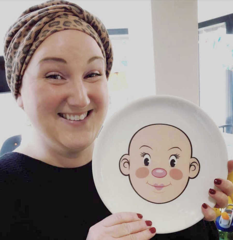 bald woman with a plate with a bald head painted on it