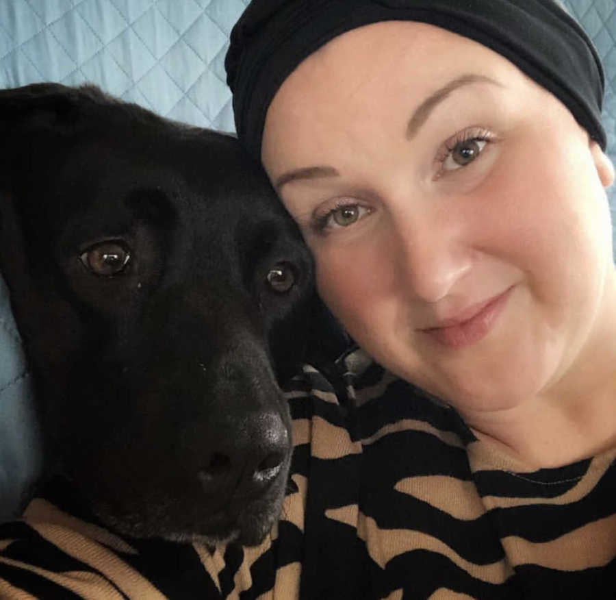 woman with head covering and dog